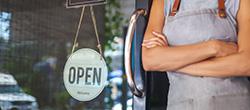 Frau steht vor Glastür mit Ladenschild mit der Aufschrift geöffnet