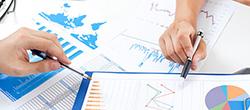 2 Hände zeigen mit Kugelschreibern auf Statistiken