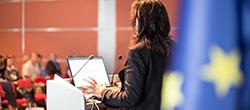 Frau steht vor einem Rednerpult und hält eine Rede, Europaflagge im Hintergrund